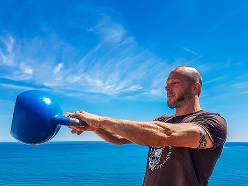 A man working out with a kettlebell by the ocean.